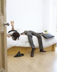 Man too tall for his bed with feet hanging over end